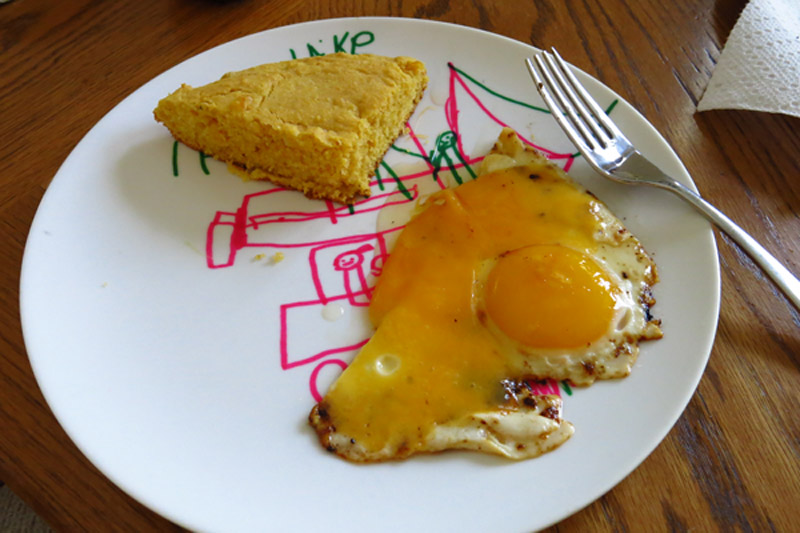 Fresh corn bread with a cheesy sunny side up egg for breakfast.
