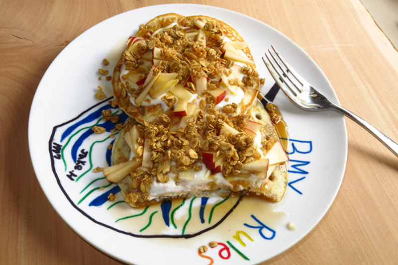 Homemade yogurt atop pancakes with diced apples, granola, and maple syrup.