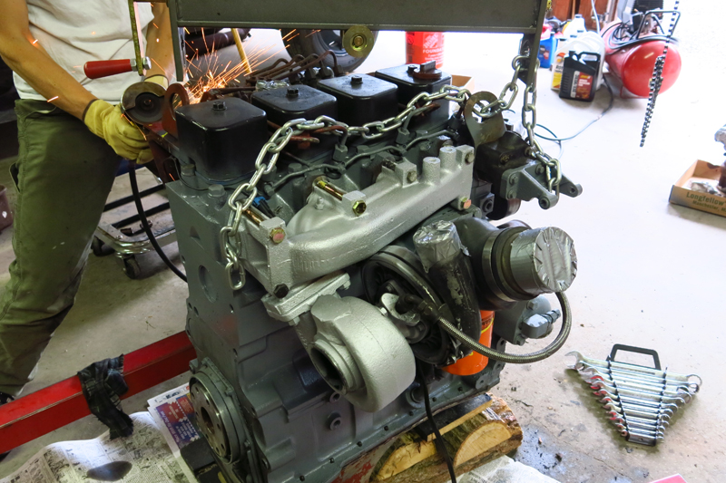 Engine painted and cleaned up with new seals and some differed maintenance.  Adrienne cuts a bracket to accept the throttle linkage.